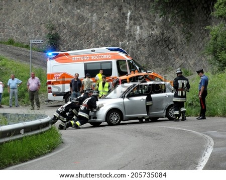 BRESSANONE BRIXEN, ITALY - MAY 2, 2011: Emergency car turned upside down after road crash collision with intervention of Firefighters and Paramedics in Bressanone Brixen, on May 2, 2011 - stock photo