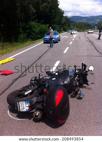 BRESSANONE BRIXEN, MAY 31, 2011: Motorcycle accident that happened on the road after car collision. Motorbike crash collision hit by car with injured motorbiker in Bressanone Brixen on May 31, 2011.  - stock photo