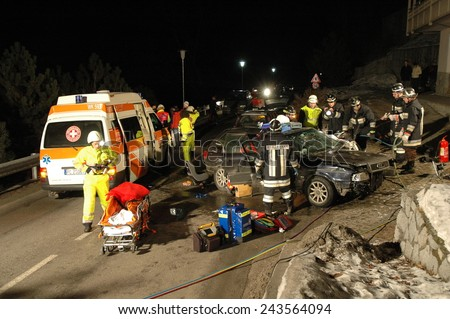 BRESSANONE, ITALY - JANUARY 12, 2015: Firefighters and Paramedics at work in the night after hard collision between two cars on the road. Car accident after hitting a patch of ice on January 12, 2015. - stock photo