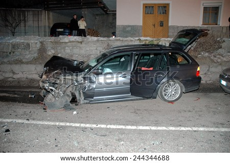 BRESSANONE, ITALY - JANUARY 12, 2015: Scene of frontal collision in the night between two cars on the road in winter time. Car accident after hitting a patch of ice on January 12, 2015. - stock photo