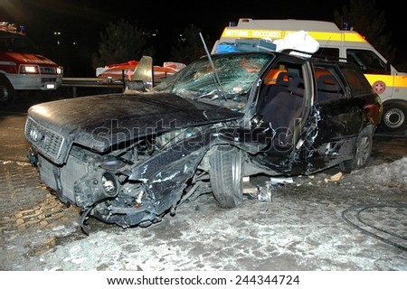 BRESSANONE, ITALY - JANUARY 12, 2015: Scene of frontal collision in the night between two cars on the road in winter time. Car accident after hitting a patch of ice on January 12, 2015.