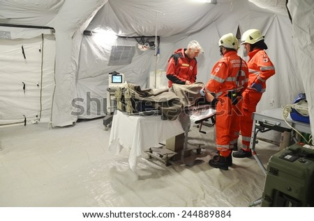 BRESSANONE, ITALY - NOVEMBER 16, 2014: A doctor examines patients inside a operating room camp for flood affected victims. Hospital field tent for the first AID on November 16, 2014. - stock photo