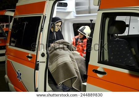 BRESSANONE, ITALY - NOVEMBER 16, 2014: A doctor examines patients inside an ambulance car near a hospital field tent for the first AID on November 16, 2014. - stock photo