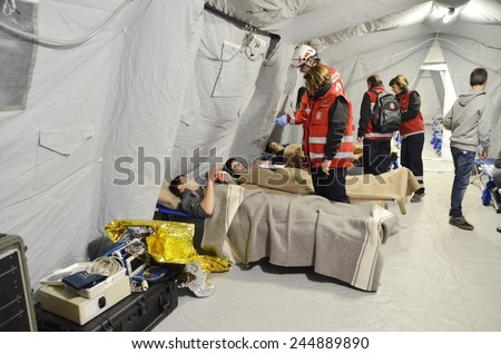 BRESSANONE, ITALY - NOVEMBER 16, 2014: A hospital field tent for the first AID, a mobile medical unit of red cross. Camp room for the rescue of injured people after flood on November 16, 2014. - stock photo