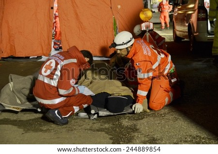 BRESSANONE, ITALY - NOVEMBER 16, 2014: Doctor checking patient on the stretcher inside a hospital field tent for the first AID. Camp room for the rescue of injured people on November 16, 2014. - stock photo