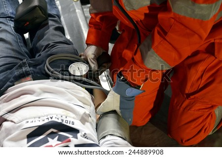 BRESSANONE, ITALY - NOVEMBER 16, 2014: Doctor measuring blood pressure of male patient inside a hospital field tent for the first AID. Camp room for the rescue of injured people on November 16, 2014. - stock photo