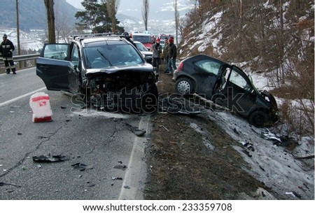 BRESSANONE, ITALY - NOVEMBER 25, 2014: Firefighters at work after collision between three cars on the road in winter time. Car off road after hitting a patch of ice in Bressanone on November 25, 2014.