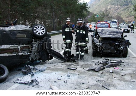 BRESSANONE, ITALY - NOVEMBER 25, 2014: Firefighters at work after collision between two cars on the road in winter time. Car flipped and rolled after hitting a patch of ice on November 25, 2014