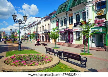 Brest, Belarus - May 8, 2015. The pedestrian Sovetskaya Street. The central street with shops and entertainment, flower bed with pink flowers in the foreground. - stock photo