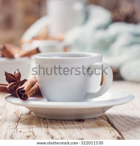 brewed coffee in white porcelain Cup and spices (cinnamon and anise) on a wooden table - stock photo