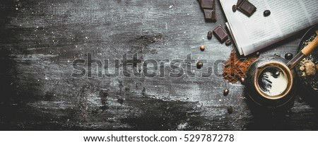 Brewed coffee pot with fresh newspaper and bitter chocolate. On black rustic background.
