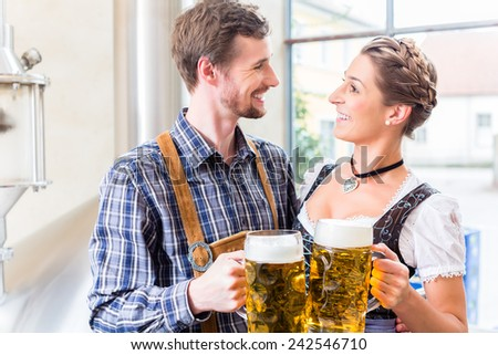 Brewer and woman toasting in beer brewery - stock photo