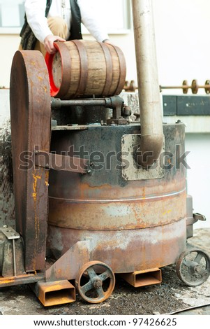 brewer in his brewery is traditionally sealing a beer barrel with tar pitch - stock photo