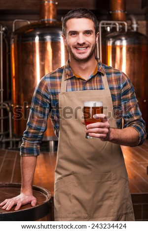 Brewing the best beer. Happy young male brewer in apron holding glass with beer and smiling while standing in front of metal containers - stock photo