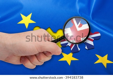 Brexit - Hand With Magnifying glass Silky Flag Over European Union EU Flag Drapery With Puzzle Piece With Great Britain - stock photo