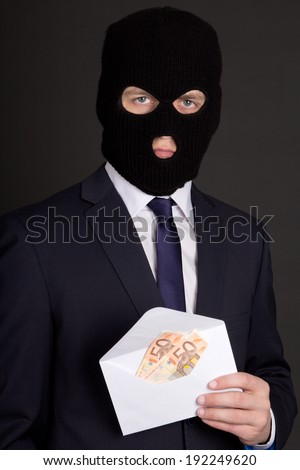 bribery concept - man in business suit and black mask holding envelope with euro banknotes - stock photo