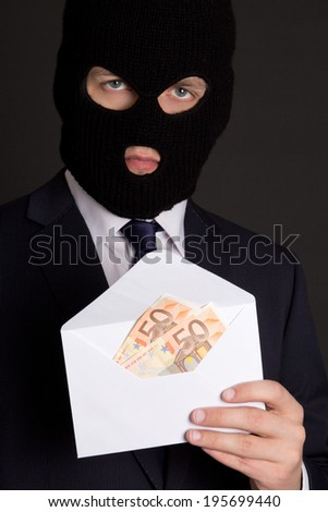 bribery concept - masked man in business suit holding envelope with euro banknotes - stock photo