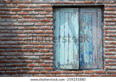 brick and old window blue color with shadow and light. - stock photo