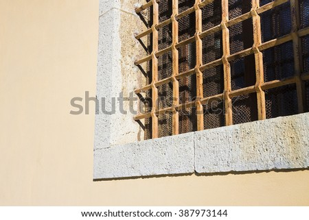 Brick and stone wall with an old rusty grating - stock photo