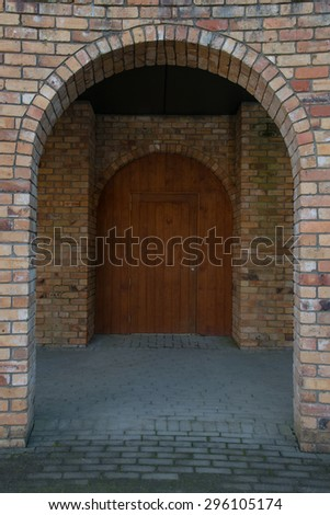Brick archway and a wooden antique door make for a lovely photo for many applications, ideas, and concepts about anything for entering doors in our lives or closing doors. - stock photo