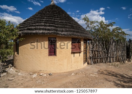 Brick-build round hut with thatched roof and wooden fence, Africa