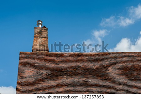 Brick chimney on roof with blue sky in background.