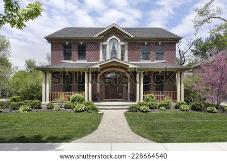 Brick home with white columns and arched entry - stock photo