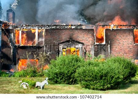 brick house burning to the ground - stock photo
