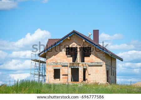 Brick House Construction Site. Building Construction Ceramic Brick House.  Unfinished Home Construction With Roof