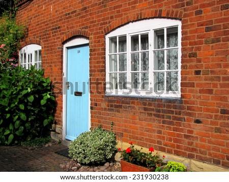 Brick house with blue door - stock photo