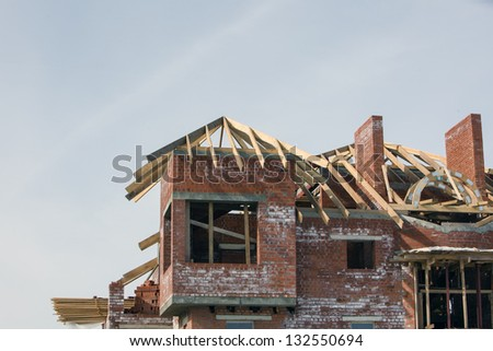 brick house with wooden roof under construction in the sky