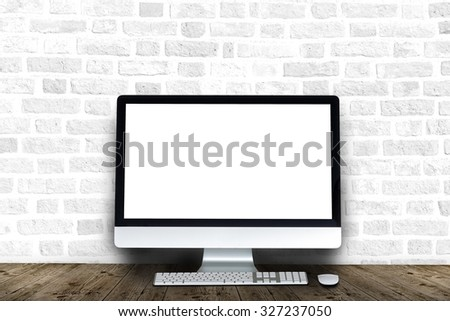 Brick interior with computer display on a wooden table - stock photo