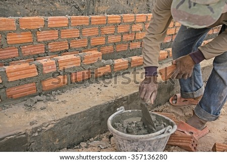 Brick layer worker at Construction site - Thailand Mason worker bricklayer installing red brick with trowel putty knife. - stock photo