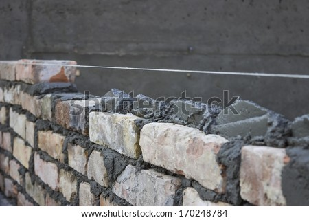 Brick laying, bricklaying spreading a bed joint. Bricklaying foundation walls, spread a mortar bed joint for building brick. - stock photo