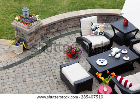 Brick paved patio with comfortable patio furniture with modern armchairs and a stool around a table set with tea and cookies alongside a low curving wall overlooking a green lawn, high angle view - stock photo