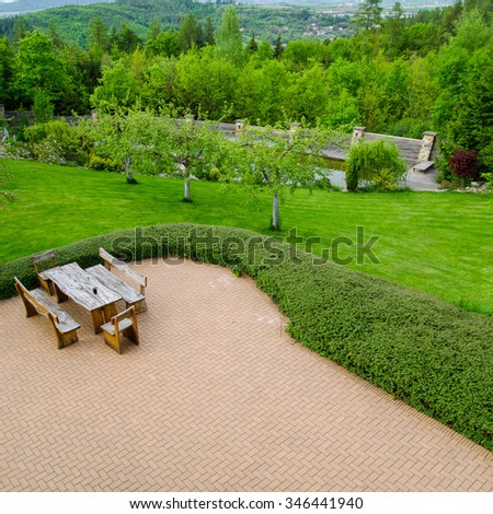 Brick paved patio with comfortable patio furniture with rustic armchairs and a stool surrounded by garden, high angle view - stock photo