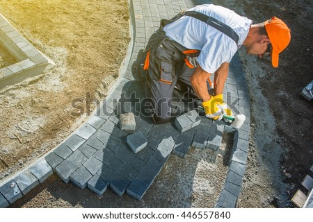Brick Paving Works. Professional Caucasian Worker Building Block Paved Hardstanding Garden Path - stock photo