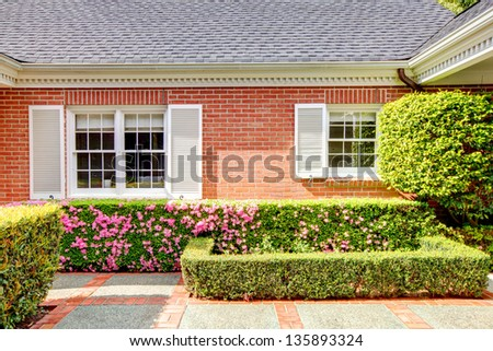 Brick red house with English garden and white window shutters. Summer landscape. - stock photo