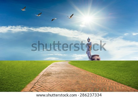 Brick road and buddha statue with sky background. - stock photo