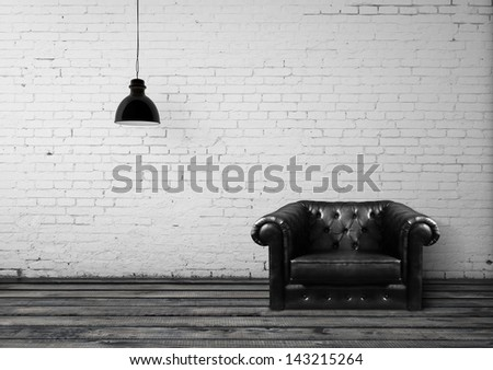 brick room with leather chair - stock photo