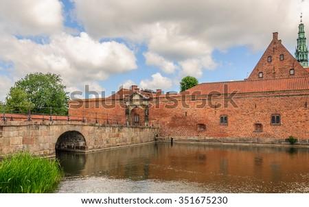 Brick stone bridge across the lake surrounding Castle Frederiksborg Slot, Hillerod, near Copenhagen, Denmark - stock photo
