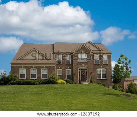 Brick Suburban Home on a cloudy spring day.