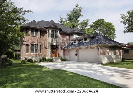 Brick suburban home with three car garage - stock photo