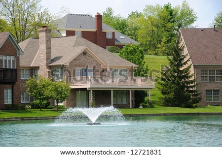 Brick Suburban Homes on a pond in the summer. - stock photo