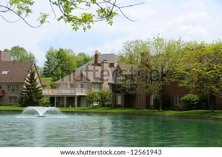 Brick Suburban Lakeside Homes in the summer. - stock photo