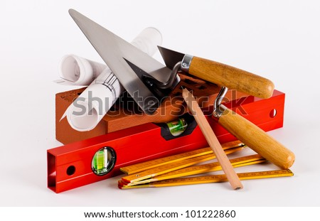 brick, tools and construction plans on white background - stock photo