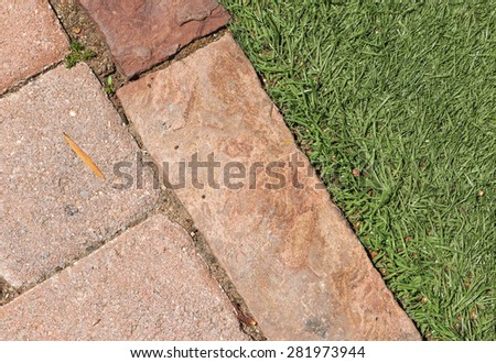 Brick walkway edge and grass close up. Rectangle shape paving stones touch blades of green grass