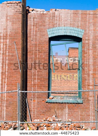 Brick wall and broken window at a demolition site