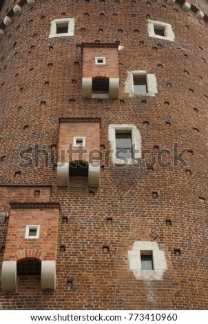Brick Wall Of An Old Building With Windows And Toilet Rooms On The Facade