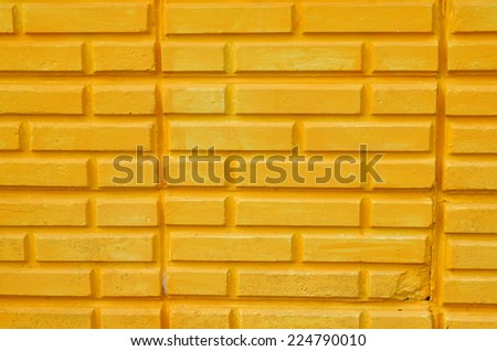 brick wall painted yellow color. - stock photo